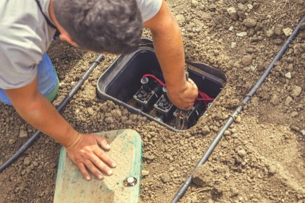 Alvaro repairing a sprinkler system valve box.